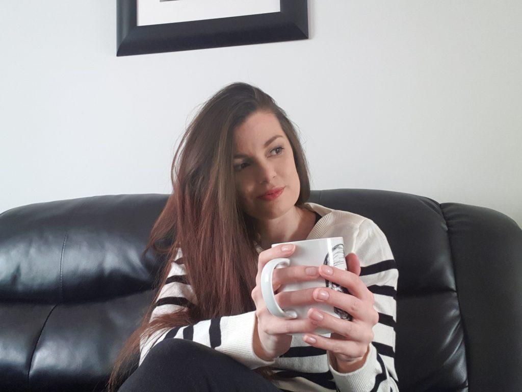 woman in stripe jumper on black sofa holding a mug