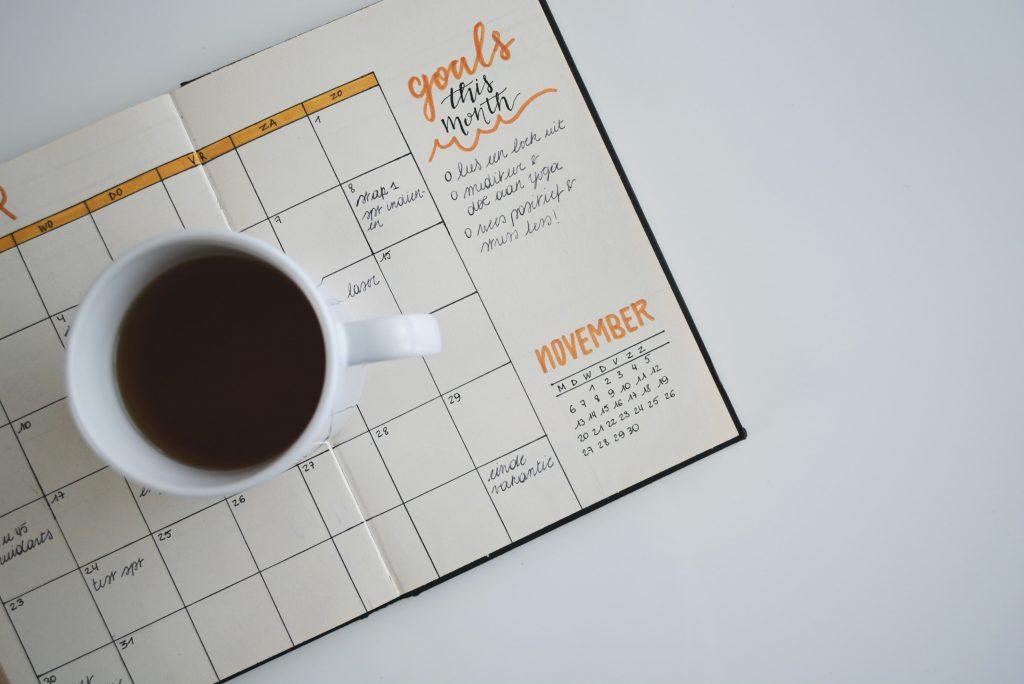 Diary open with coffee mug on top