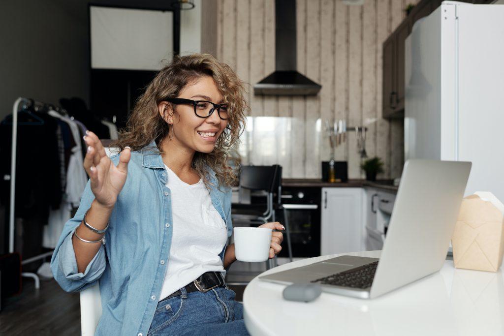 woman waving at laptop being social